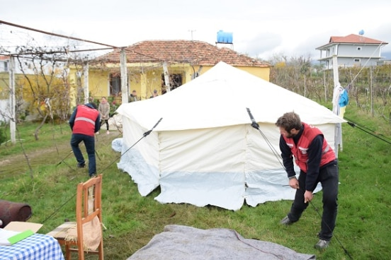 Swiss humanitarian team setting up a tent in a Kurbin village, December 3d, 2019