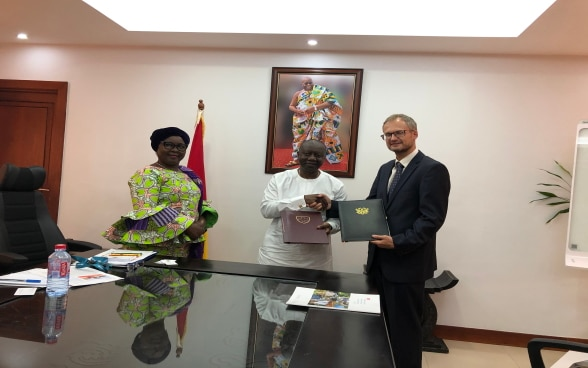 Ambassador Stalder, exchanging the signed documents with Finance Minister, Ken Ofori Atta