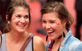 Two laughing young women with Swiss flags painted onto their cheeks.