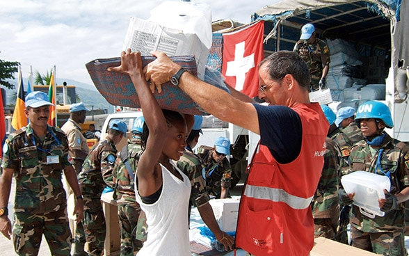 A member of the Swiss Humanitarian Aid Unit (SHA) distributes relief supplies.
