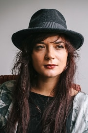 The Albanian musician Elina Duni sitting on a chair, wearing a hat.