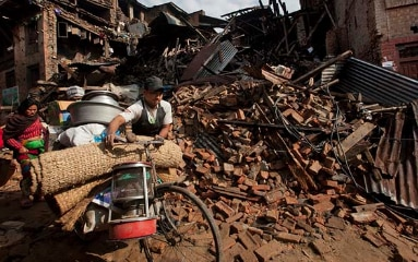 A man and woman transport their belongings through the rubble of buildings destroyed by the earthquake in Bhaktapur near Kathmandu