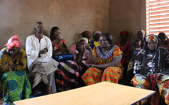 A group of Burkinabe women in a room talking.