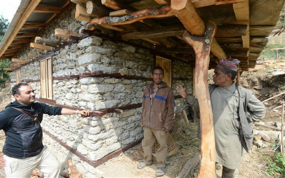 A builder talking with two villagers in front of a rehabilitated house.