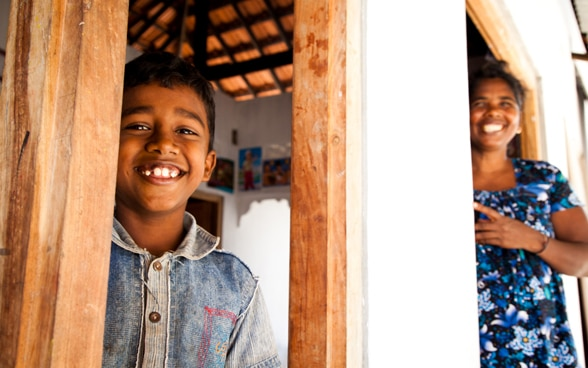 A child and a woman smiling in their rebuilt home.