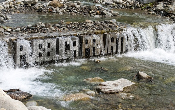 The words Pubblica, Privata are affixed in steel letters to a weir across the river.