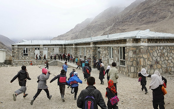 A group of children walking to school in a mountainous region.