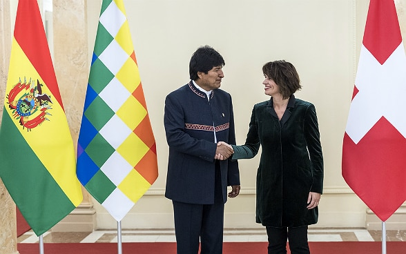 Evo Morales Ayma and Doris Leuthard shake hands in front of the national flags.