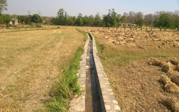 Freshly repaired irrigation channel flowing through two dry fields