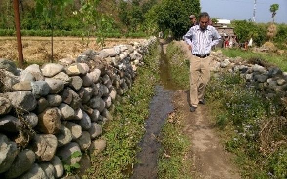 Two men walk along an irrigation channel beside a stone wall inspecting its condition.
