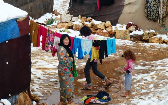 A woman in a refugee camp hangs laundry between two tents. Two children are standing next to her, with snow on the ground.