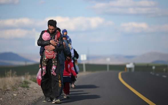 A refugee family walks along a road