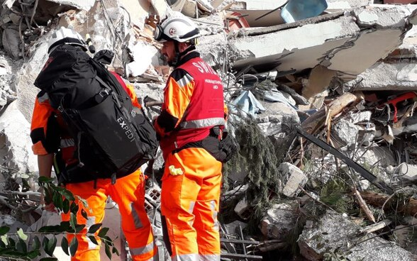 Two men oft he Swiss Humanitarian Aid Unit in front of a collapsed building.
