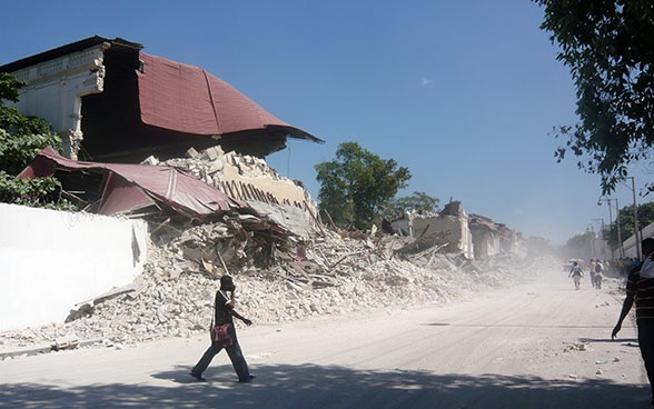A man walking past a group of houses reduced to rubble.