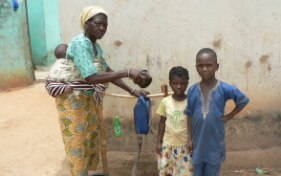 A woman with an infant on her back shows two children how to fill the makeshift handwashing device with water in front of a hut.