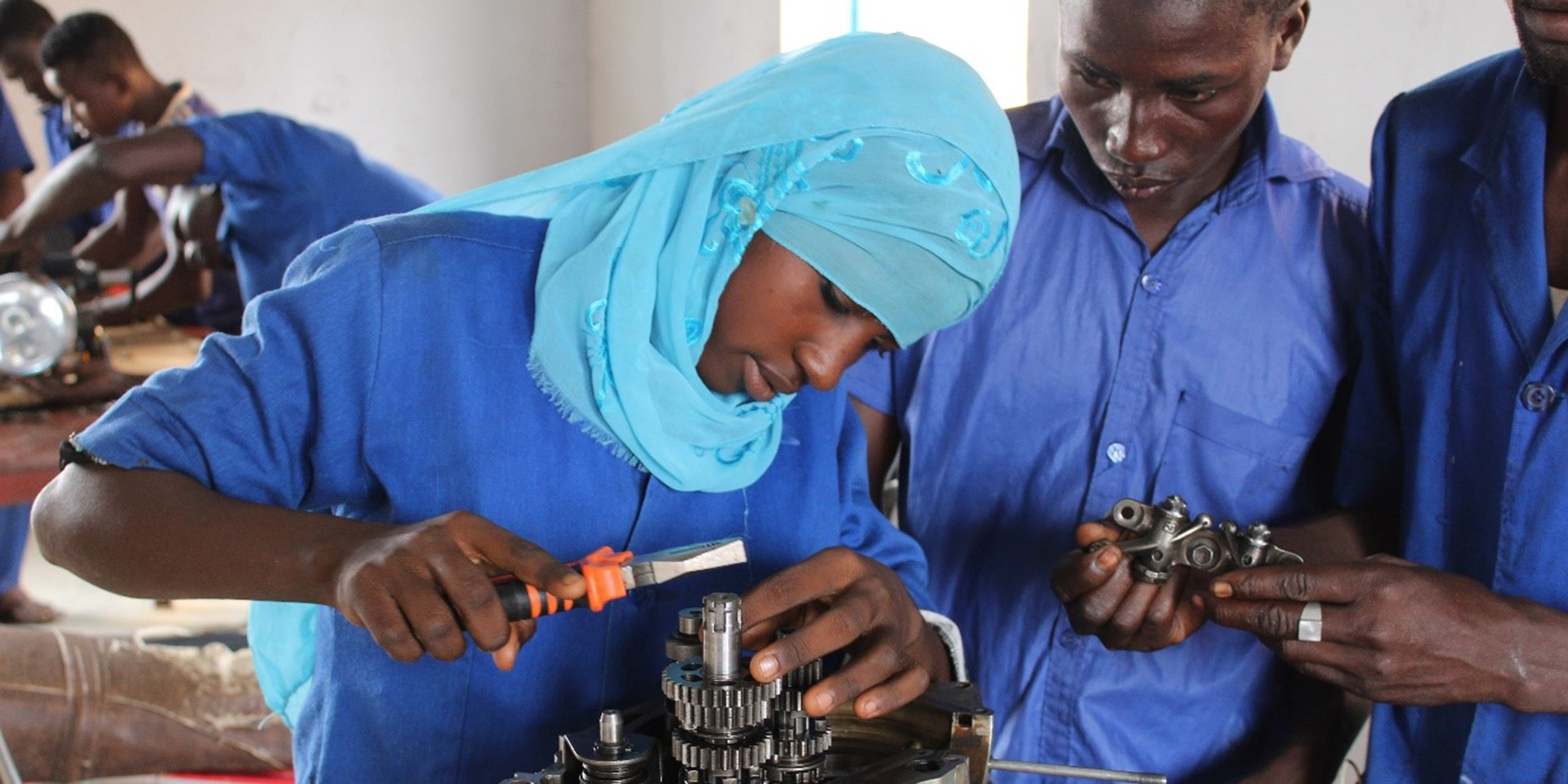 In a training workshop, a young woman with a head covering works on a mechanical component, observed by two male apprentices.