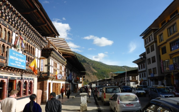 A Swiss visitor walking along a street with two local people in the Bhutanese capital, Thimpu.