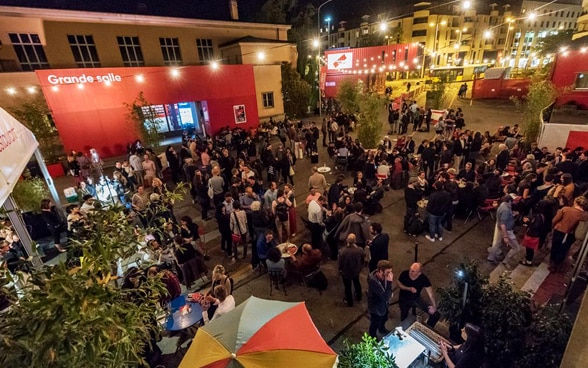 Overhead shot of the festive evening atmosphere at the festival, with film enthusiasts and documentary film professionals chatting at the festival venue.