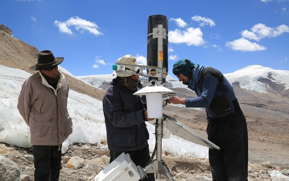 Three men install an automatic weather station in the Peruvian highlands.