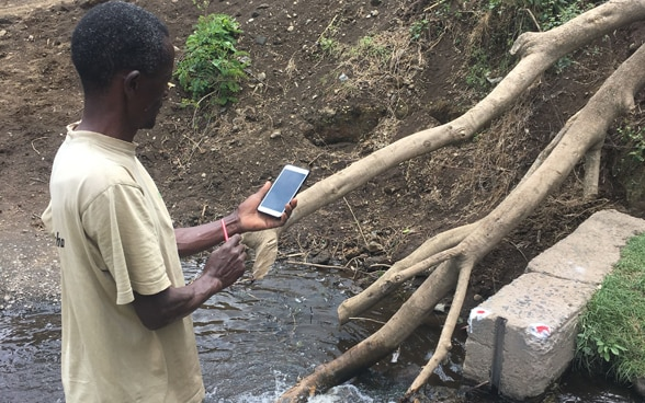 Pangani River catchment area in Tanzania uses his smartphone to measure the flow rate in an irrigation channel.