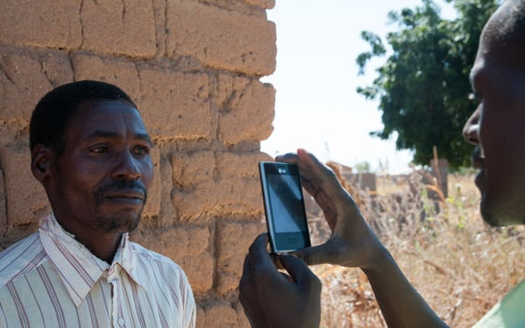A rural resident in Africa is registered in a social security system via a mobile phone.