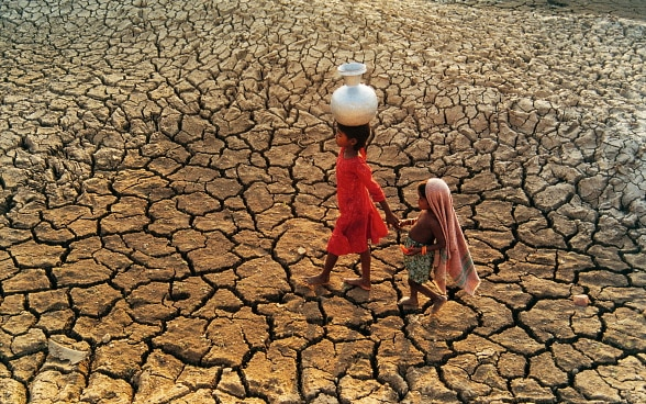 Two children with a water jug walk through a dried out riverbed.