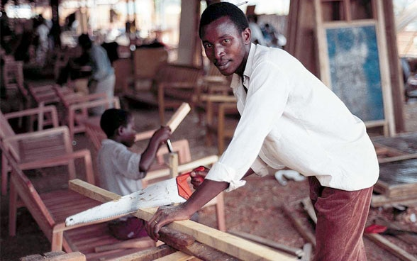 A young man sawing a wooden board.