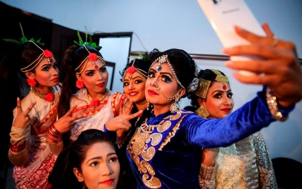 Dancers are taking photos with their mobile phones before going on stage for their performance in Dhaka, Bangladesh