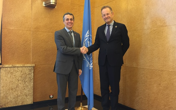 Federal Council Ignazio Cassis and Michael Moller, Director of the UN in Geneva, are shaking hands in front of an UN flag.