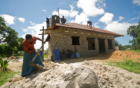 One Sri-Lankan handles a shovel in front of house under construction.