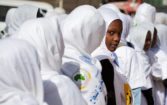 Girls wearing white head scarves stand in a row; one girl looks back.