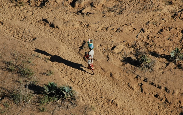 Woman walks in desert with child in her arms.