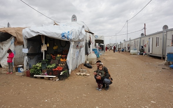 A father and daughter beside a fruit and vegetable stall in a refugee camp.