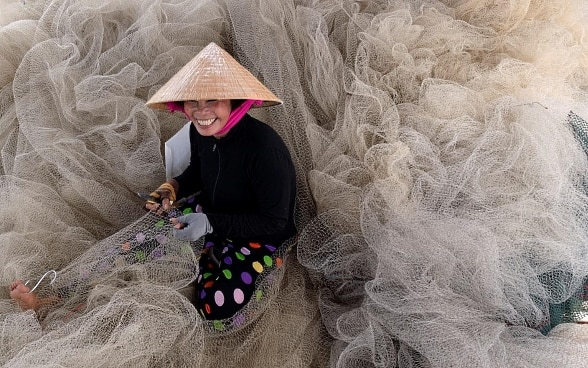 A smiling young woman sits among the fishing nets with a tool in one hand and a piece of net that she is repairing in the other.