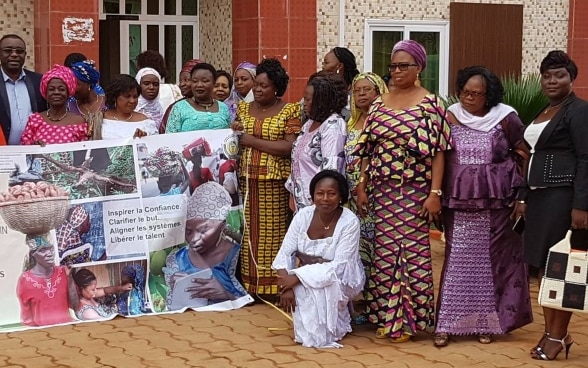 A group of women members of communal and municipal councils pose for a group photo holding a banner.