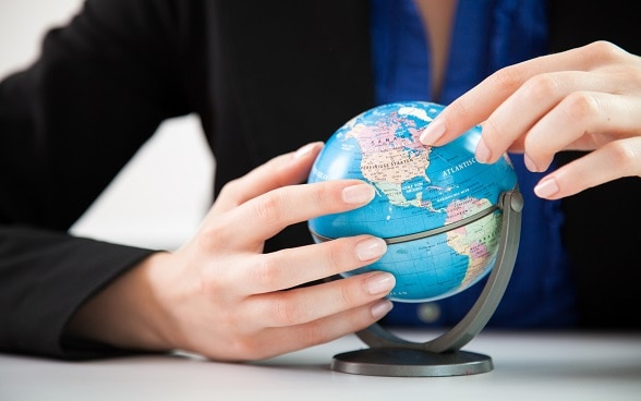 Two hands holding a small globe.