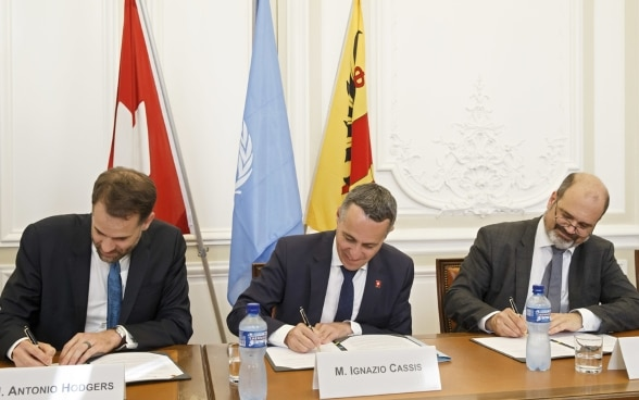 Federal Councillor Cassis, Antonio Hodgers and Sami Kanaan sit at a wooden table and sign the joint declaration.