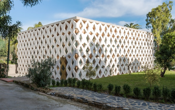 Outside view of the Swiss embassy in Algiers. The building is a white rectangular cube. The façade consists of a large lattice design of intersecting beams.