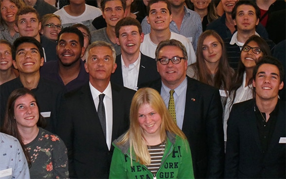 The President of the Swiss Confederation, Didier Burkhalter, standing among participants at the Youth Parliament Conference in Laufen.© FDFA