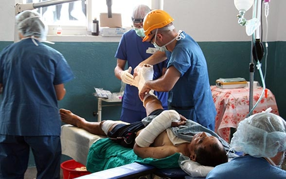 Three doctors treating a patient.