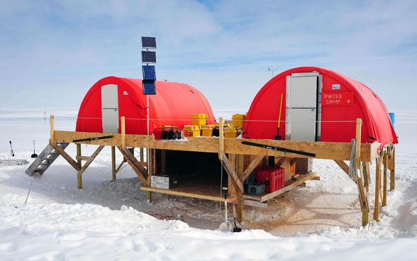 The Swiss research station in the Arctic: two red tents on a wooden platform.