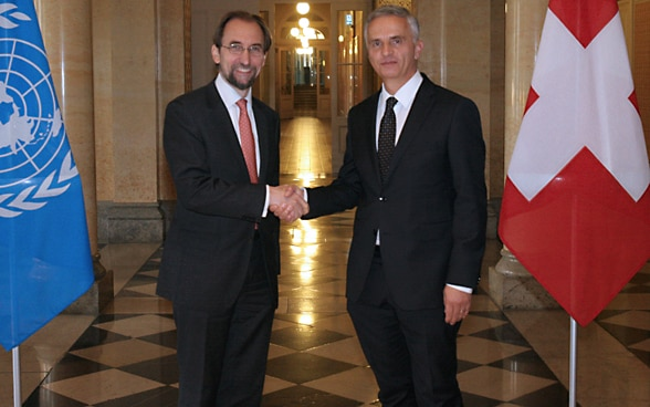 Federal Councillor Didier Burkhalter with the UN High Commissioner for Human Rights Zeid Ra'ad Al-Hussein in the Federal Palace in Bern, with the Swiss and UN flags on either side.
