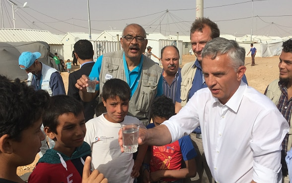 Didier Burkhalter shares a glass of water with the childrens of the Azraq refugee camp