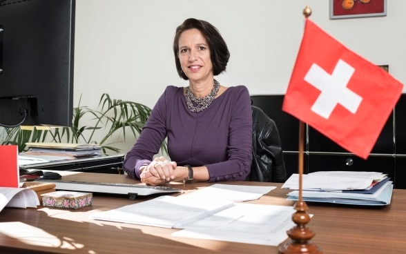 A woman with black hair, Christine Schraner Burgener, sits behind a desk with a small Swiss flag on it.