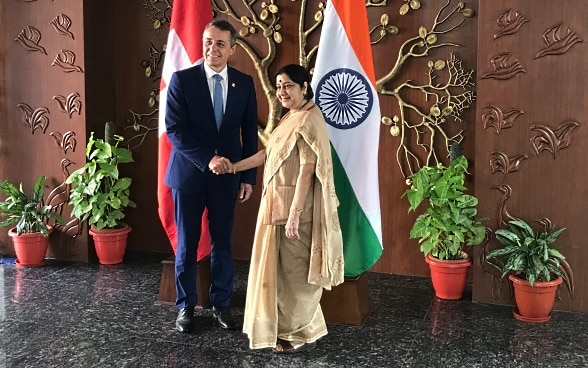 Federal Councillor Cassis shakes hands with Indian Foreign Minister Sushma Swaraj. In the background are the flags of India and Switzerland.