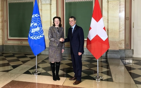 Federal Councillor Cassis shakes hands with Henrietta Fore. In the background the flags of Switzerland and the UN can be seen.
