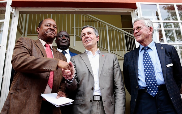 Federal Councilor Ignazio Cassis shakes hands with Zimbabwean Minister of Health Obadiah Moyo, left, while Professor Ruedi Luthy, founder of a Swiss-funded clinic, looks on during his visit.