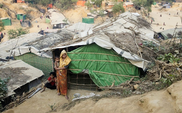 A woman and her child stand in front of a provisional cabin in the refugee camp Cox's Bazar in Bangladesh.