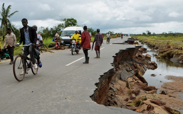 Locals try to drive on the remains of the main road, after cyclone Idai.