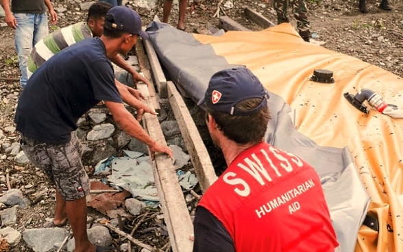A member of the Swiss Humanitarian Aid Unit helps the local population rebuild water infrastructure after a catastrophe.